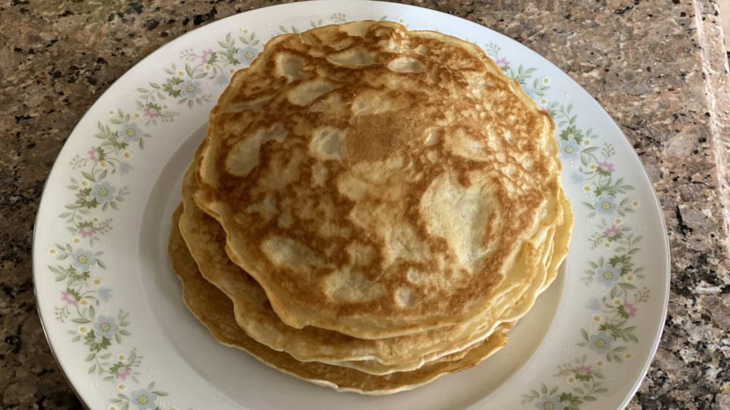 A stack of fresh homemade Filipino hotcakes on a dish with flowers