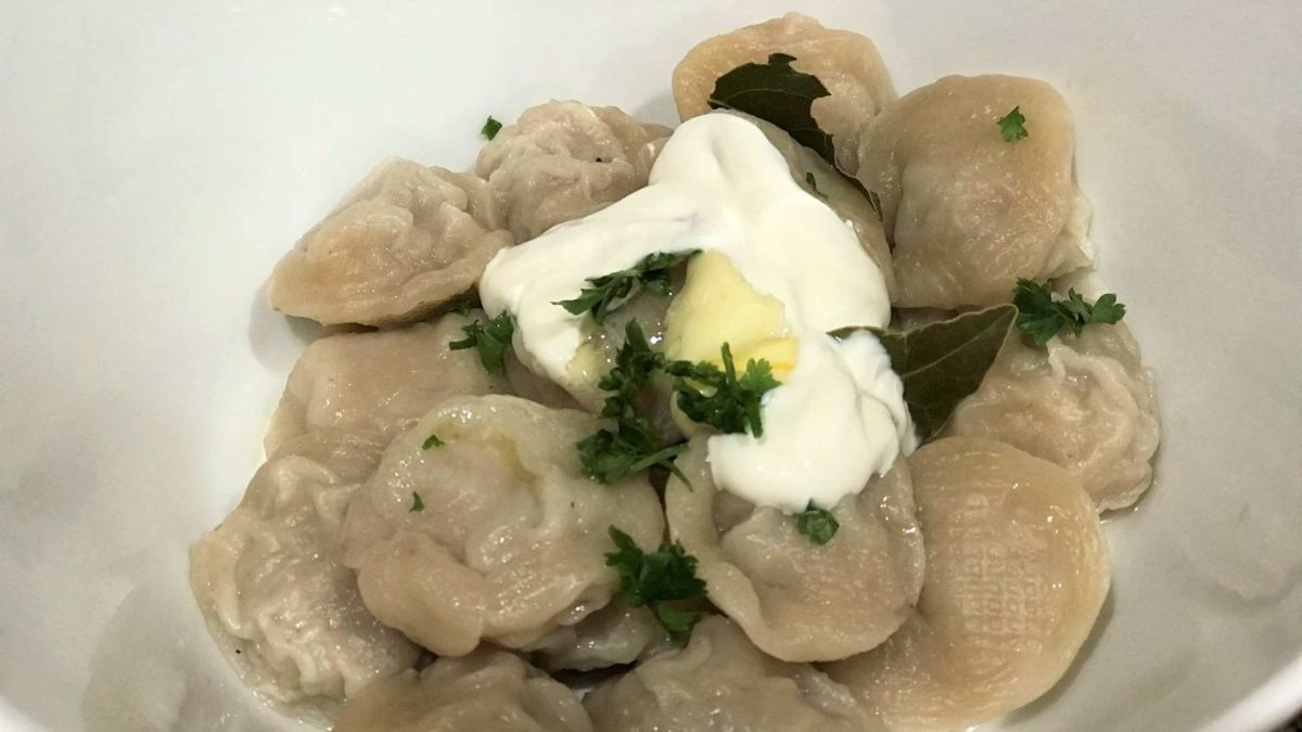 Homemade cooked pelmeni with sour cream in a bowl