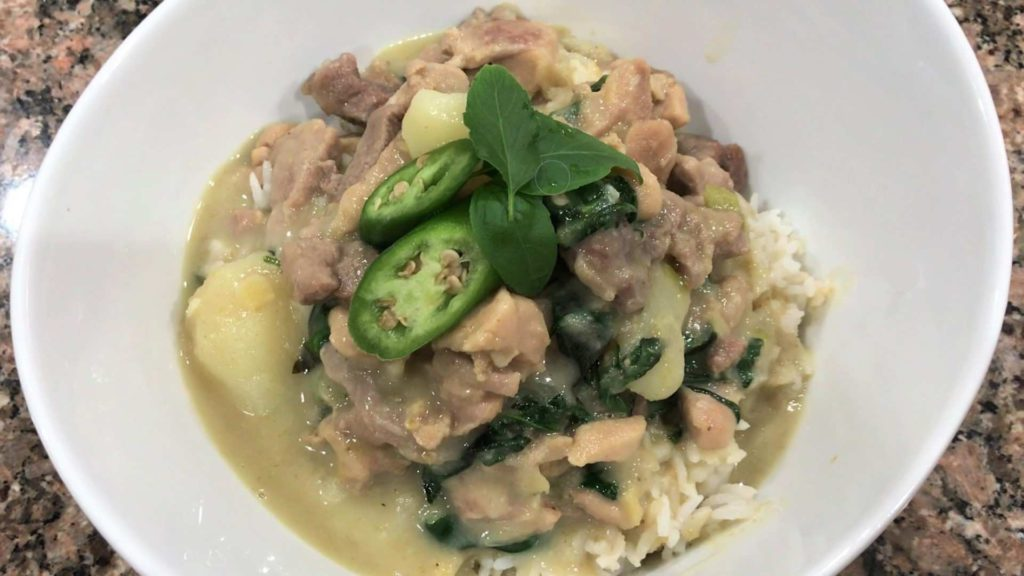 homemade thai green curry in a bowel with fresh basil and peppers
