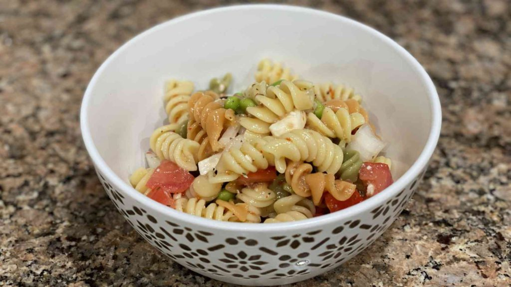 Pasta salad with onions, olives, tomato, feta cheese, and edamame.